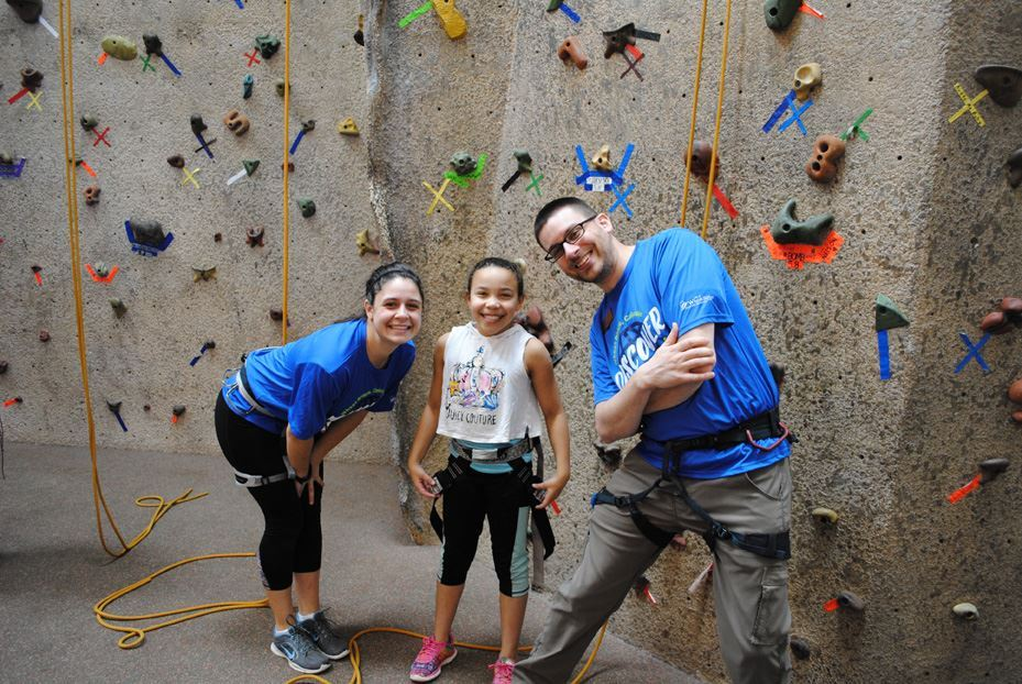 Two adults and a child by the rock climbing wall