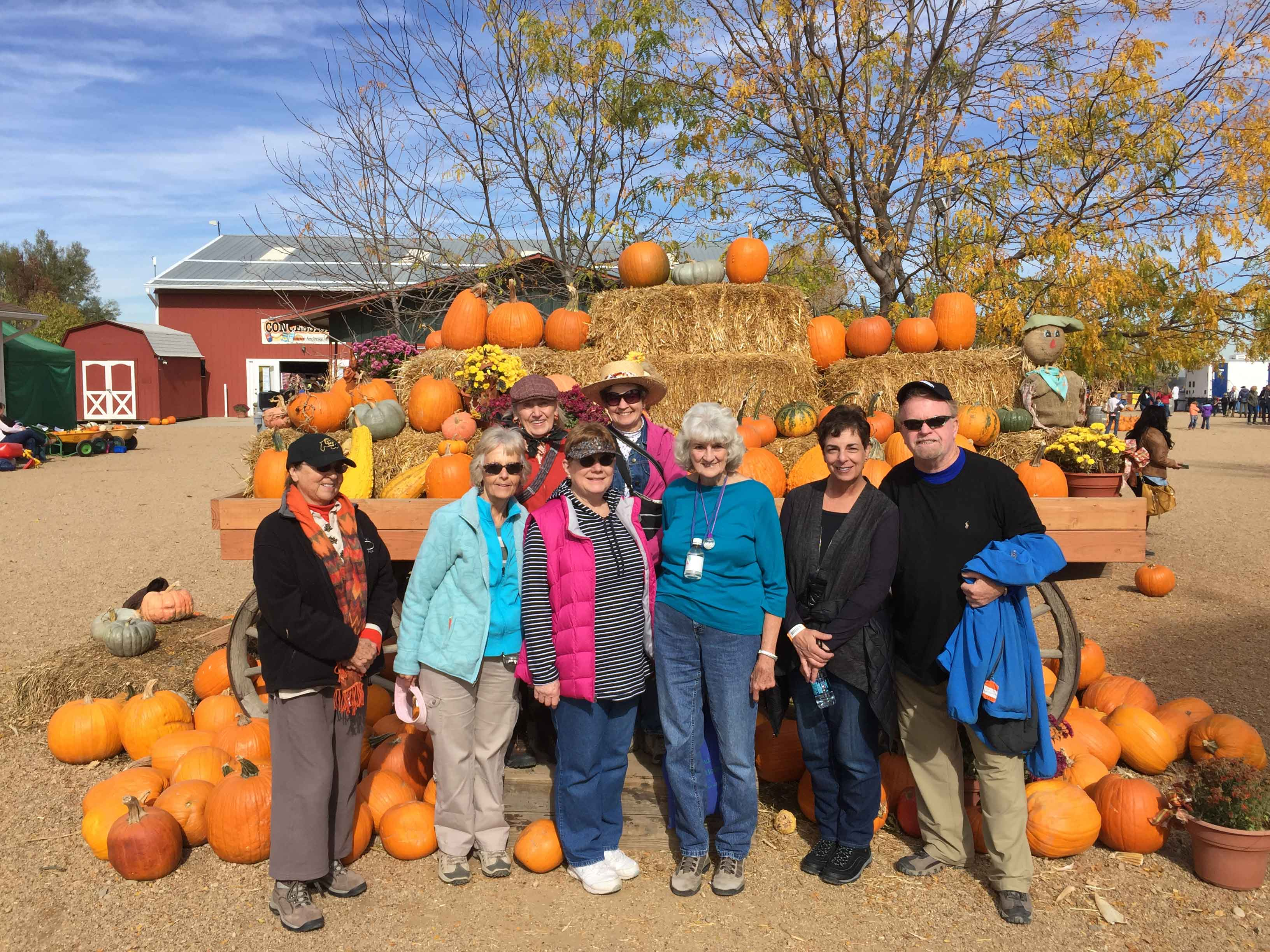 Adults posing in front of stacks of hay bails and pumpkins