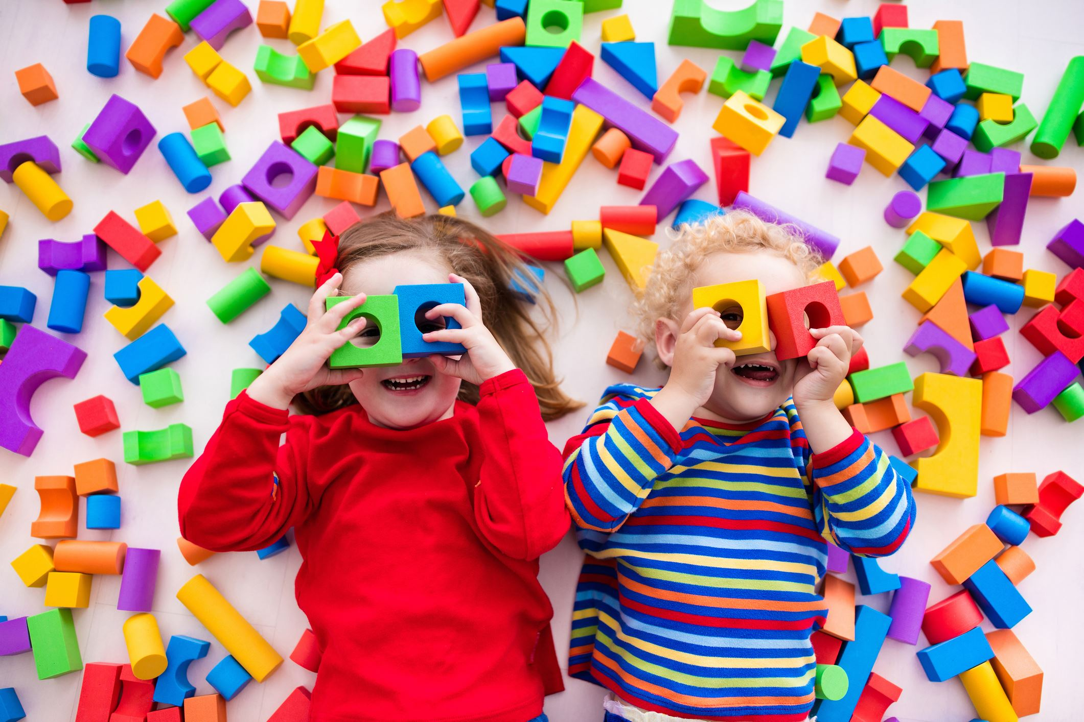 Two kids playing with colorful foam blocks