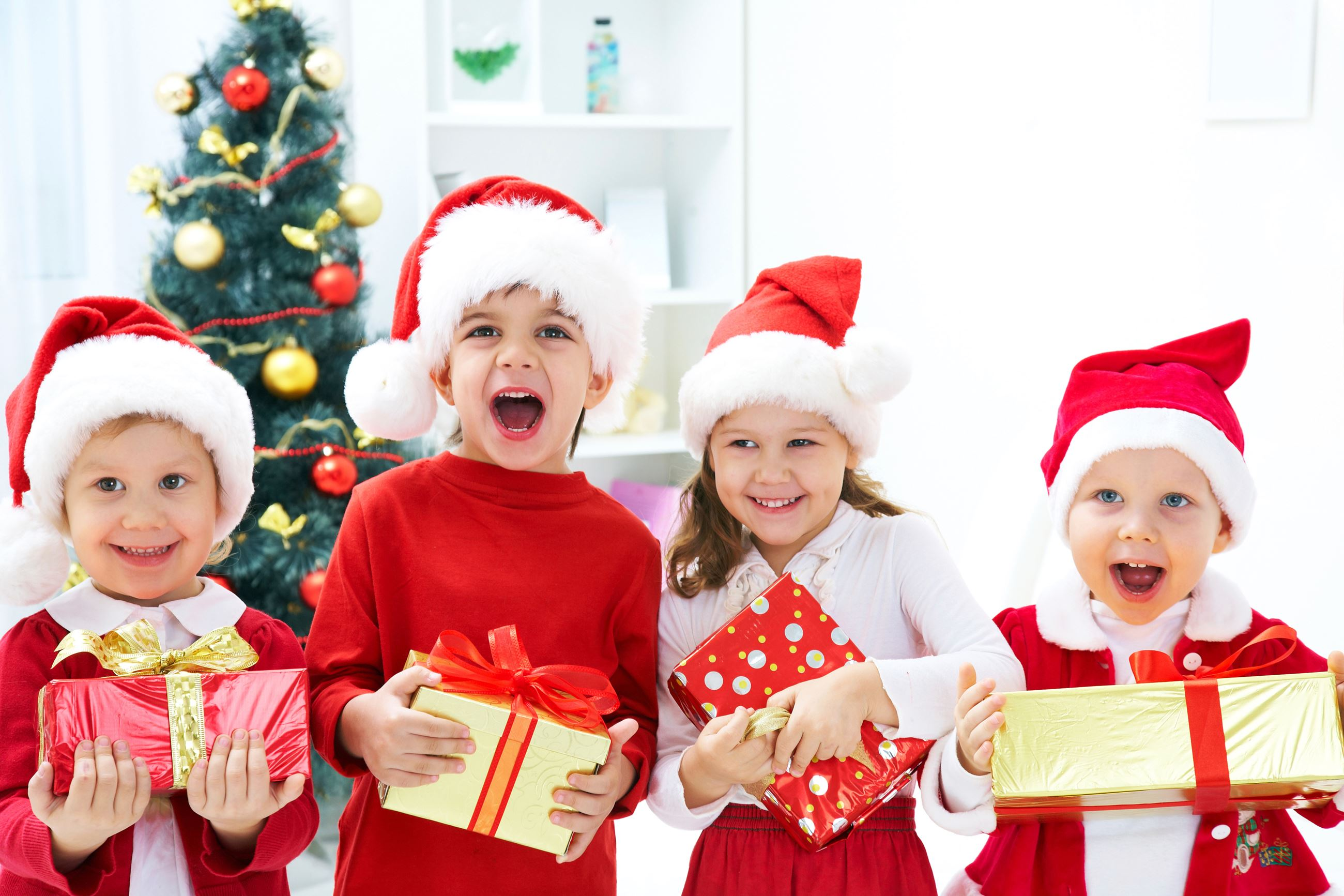 Four young kids wearing Santa hats and holding presents
