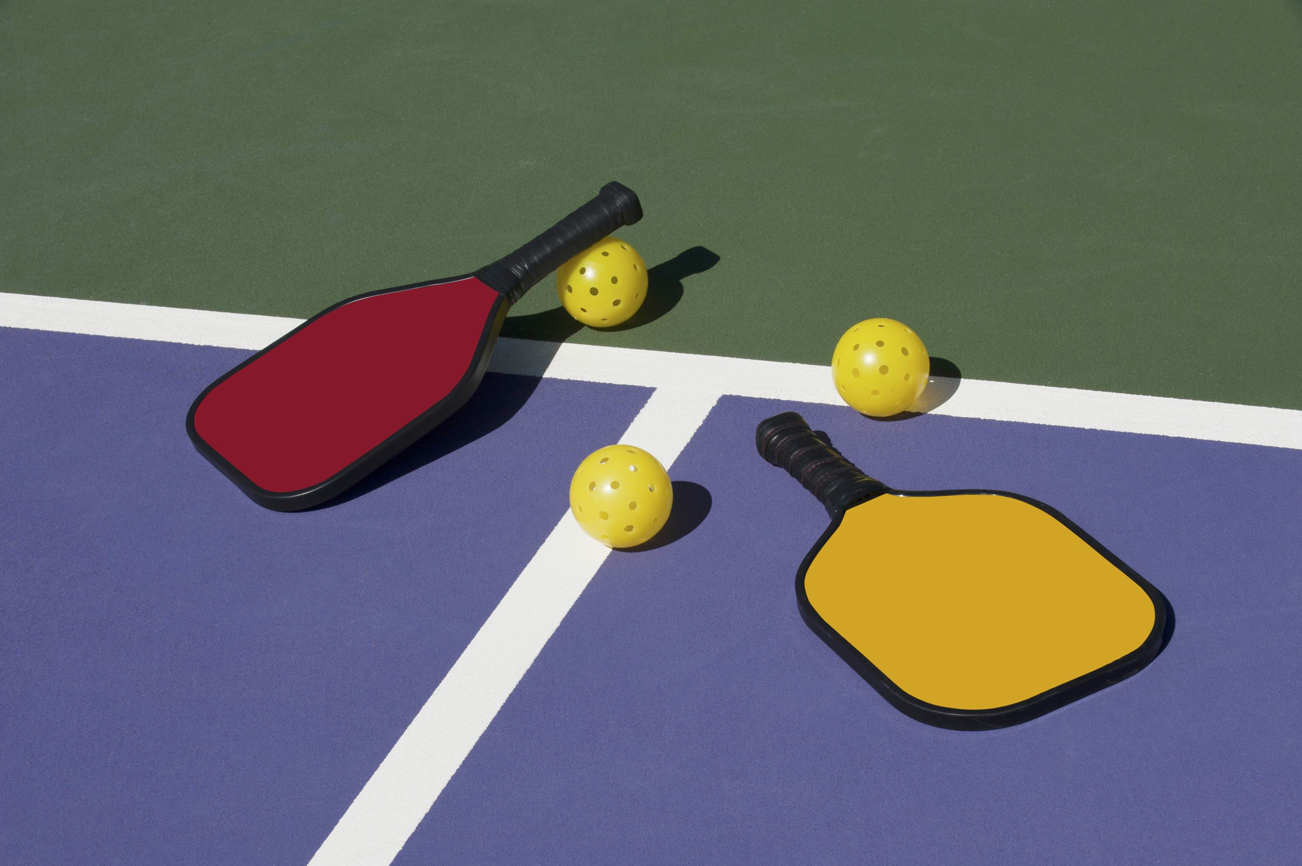 Pickleball balls and raquets laying on court