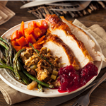 Beautifully plated dinner with sliced turkey, stuffing, sweet potatoes, green beans and cranberry sa