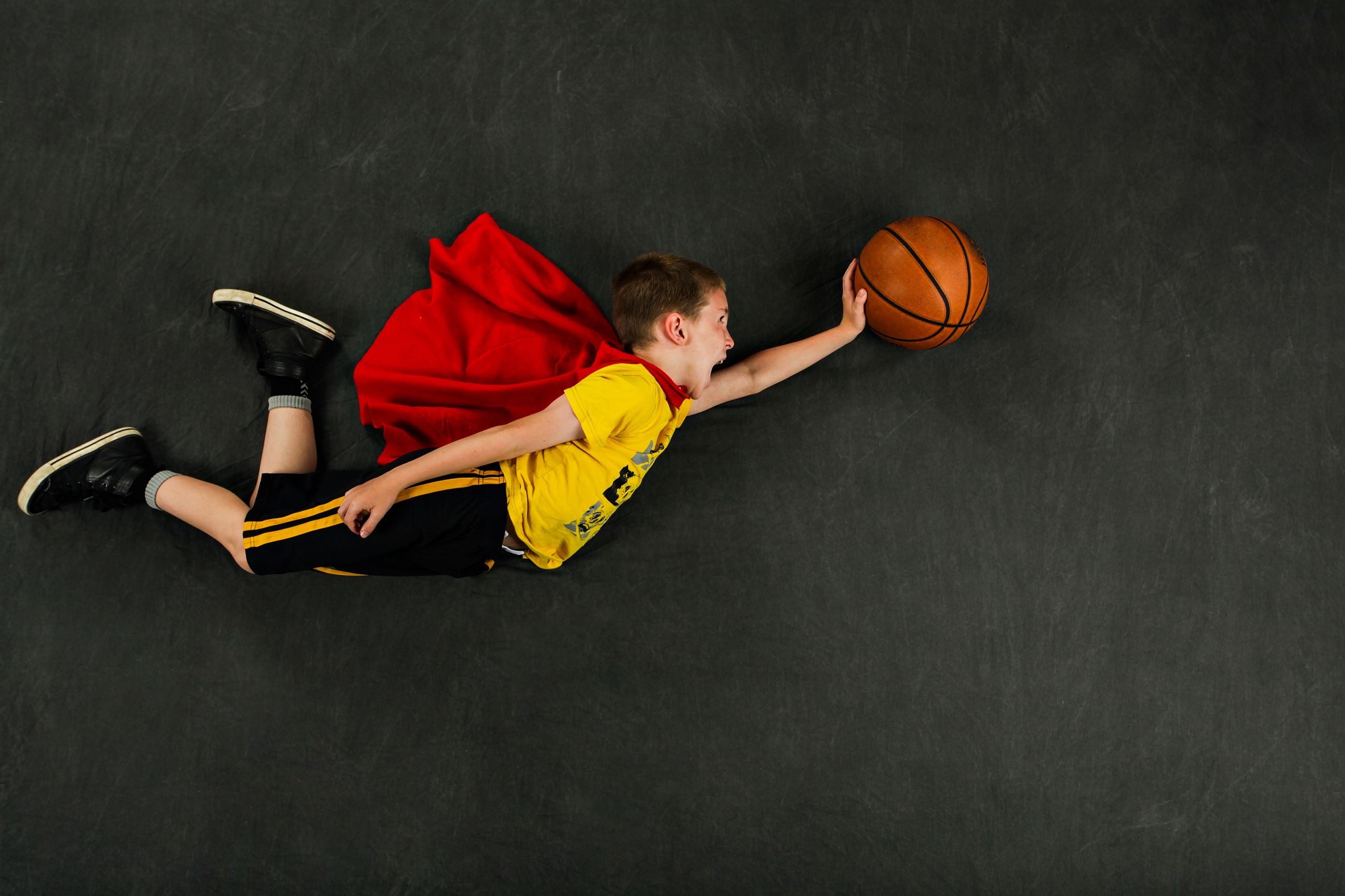 Boy wearing a cape and flying through the air with basketball