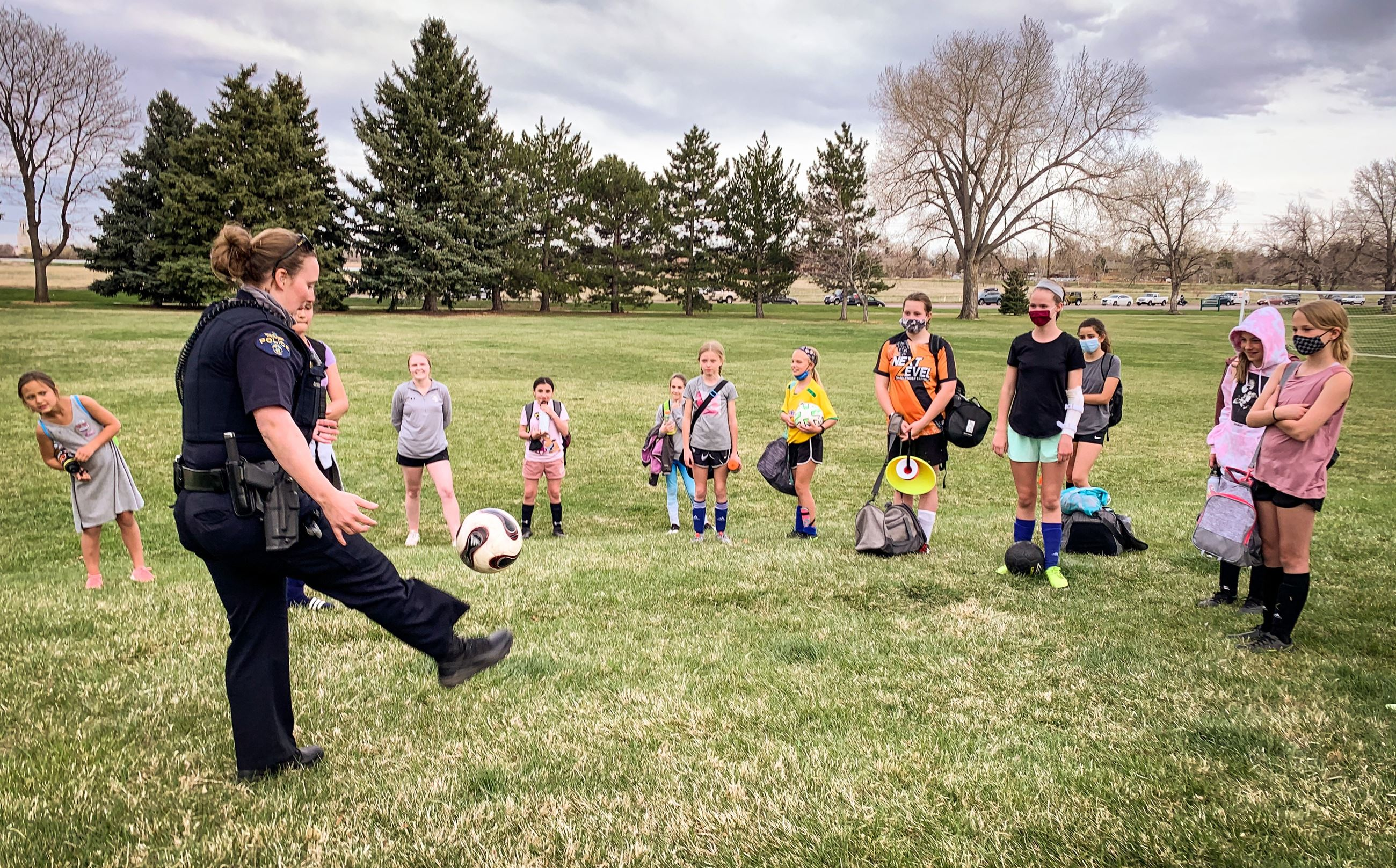 Officer  Hooper kicks it with Wheat Ridge Soccer Team